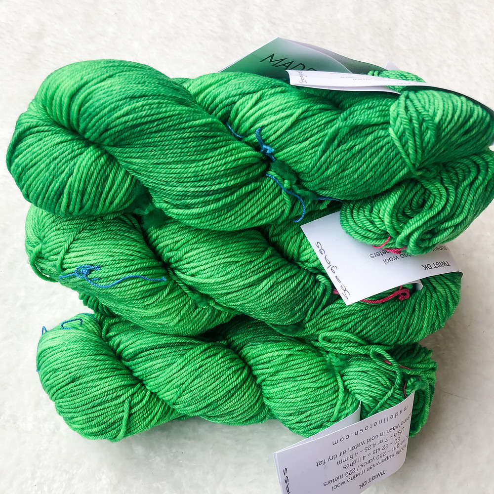 A stack of bright green skeins of yarn on a white background.