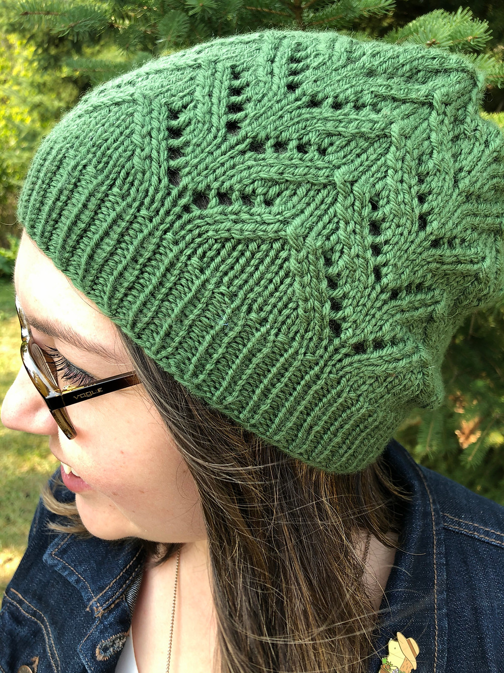 A close up of a woman wearing a green knit lace hat, with her gaze toward her right shoulder.