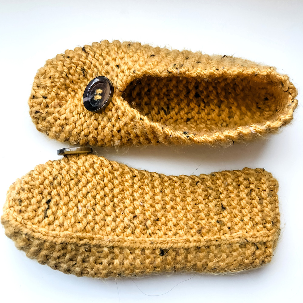 A pair of knit slippers in a mustard yellow yarn against a white background.
