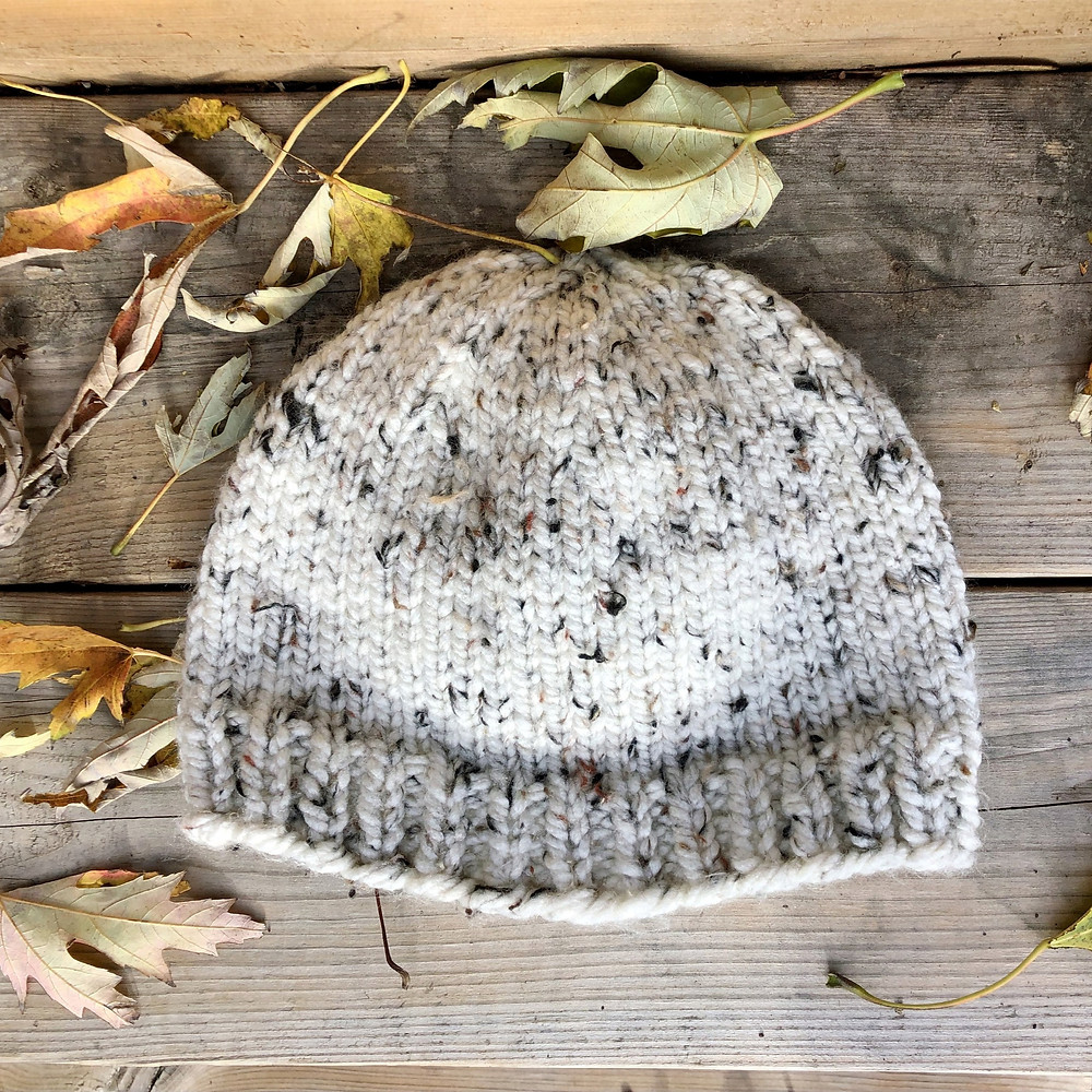A white knit hat laying flat against a wooden background with fallen leaves around it.