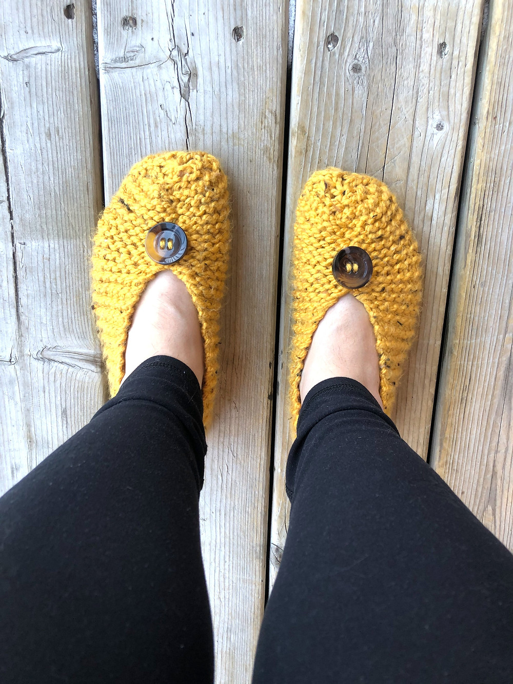 A pair of feet wearing yellow knit slippers against a wooden background.
