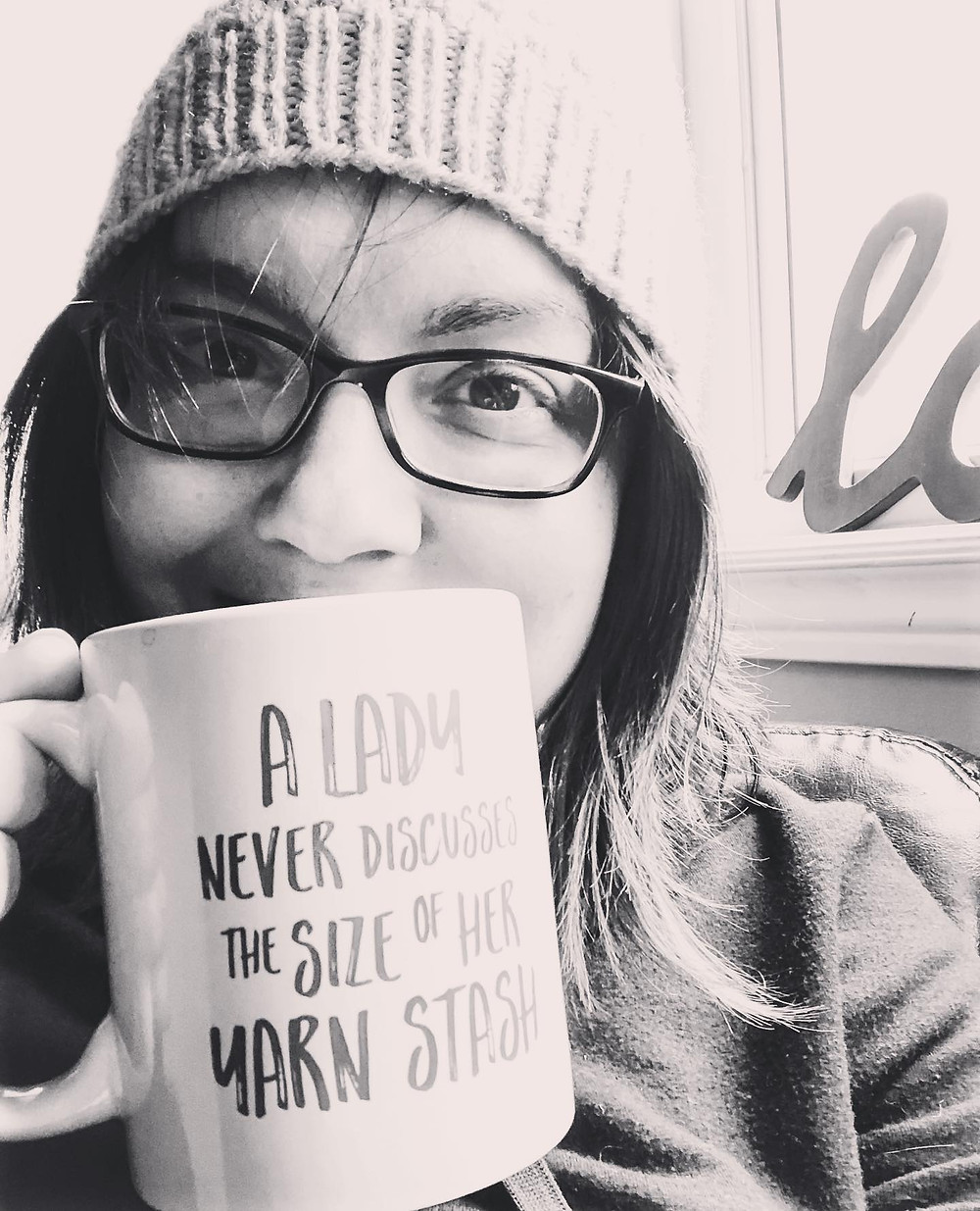 """A black and white photo of Nicole, a woman with brown hair and glasses, wearing a knit beanie and holding a coffee mug by her mouth. The mug has a caption that says """"A lady never discusses the size of her yarn stash."""""""