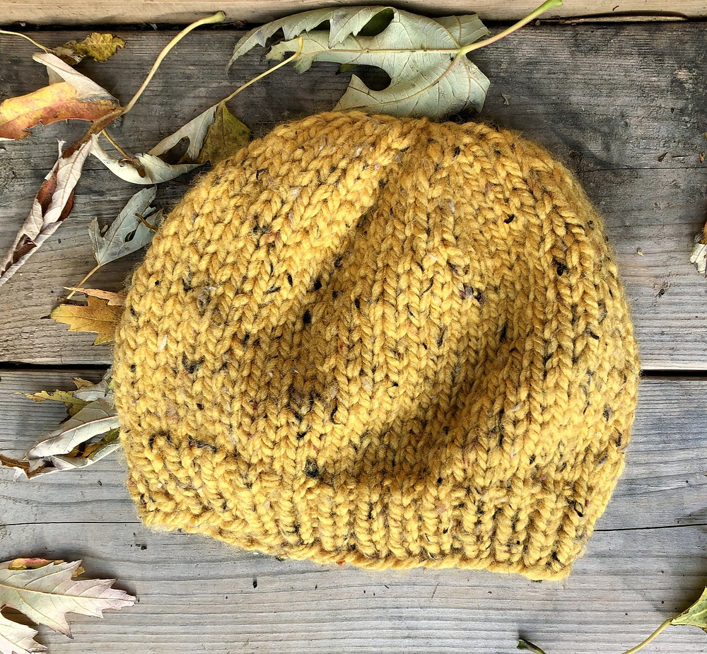 A yellow knit hat laying flat on a wooden background with fallen leaves around it.