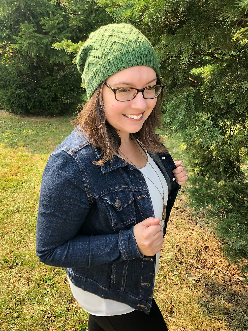 A woman with brown hair and glasses, standing outdoors wearing a green knit hat with lace detail, a denim jacket and white blouse. She is holding open the jacket with her hands and her gaze is down toward her right side.