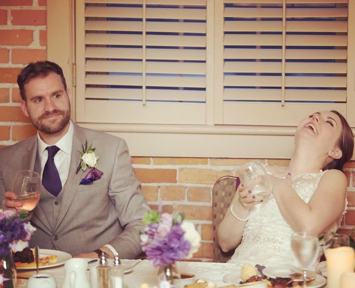 A bride and groom sitting at a table; the bride has her head back in laughter.
