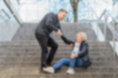 Man helping senior woman to get up while