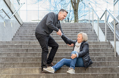 Man helping senior woman to get up while