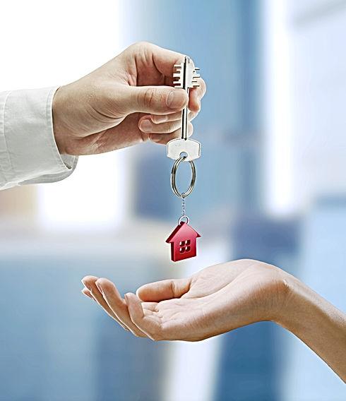 Man is handing a house key to a woman.Ke
