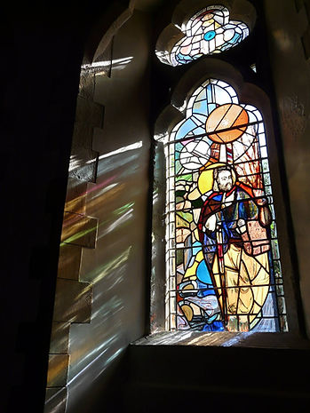 stained glass window designed painted and leaded of St James showing the light projecting onto St James's Church wall