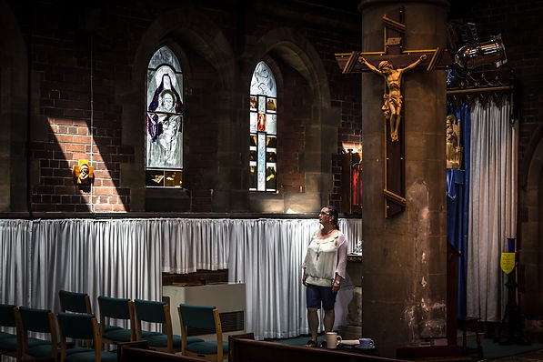Self portrate of Nathalie Leige in St Luke's Church staring up at her stained glass window creations