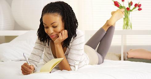 Happy black woman writing in journal.jpg