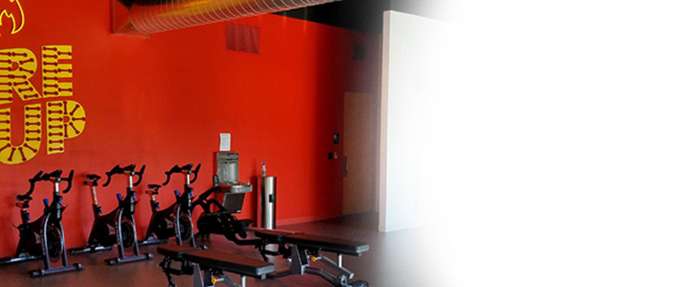 Image of red wall in commercial  gym with Stages bikes and strength equipment. Wall says Fire It Up