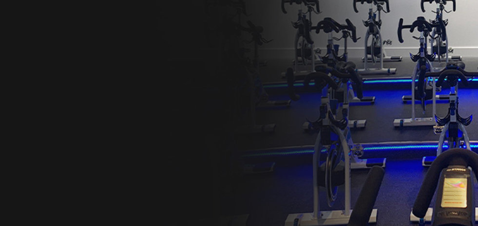 Image depicts an indoor cycling studio ready for class with Stages Indoor Bikes, Stages console
