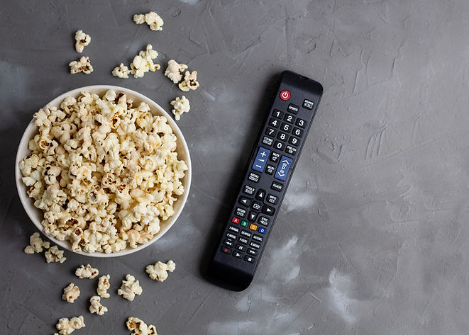 A white bowl of popcorn and TV remote on