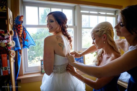Bridesmaid zipping bride's wedding dress in Vancouver, British Columbia