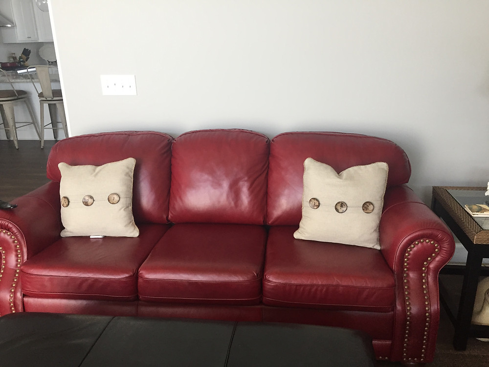 red leather couch prior to slipcovering