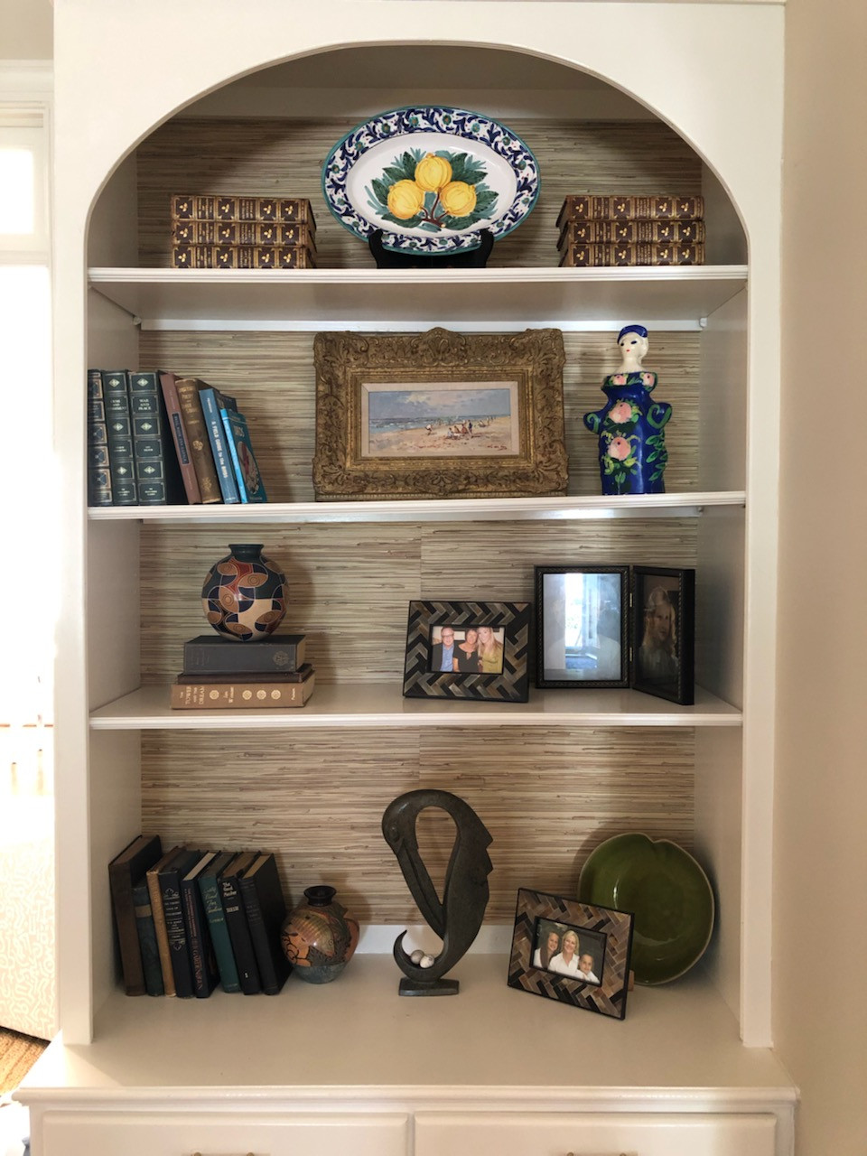 styled shelves with grasscloth