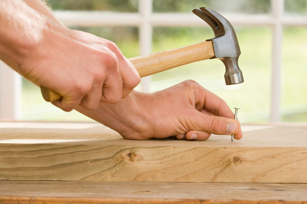 Man preparing to hammer a nail into timber
