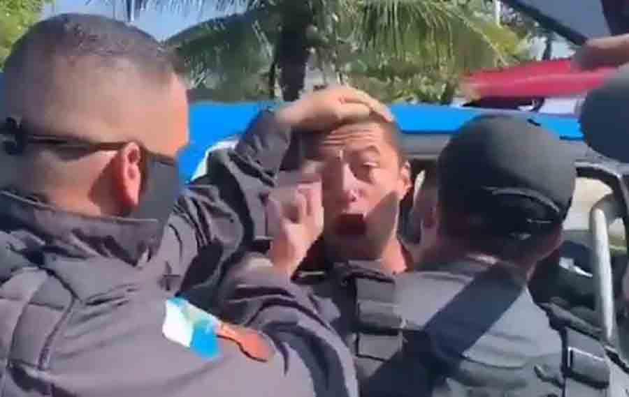 Homem gritando é detido pela PM e colocado em banco traseiro de viatura.