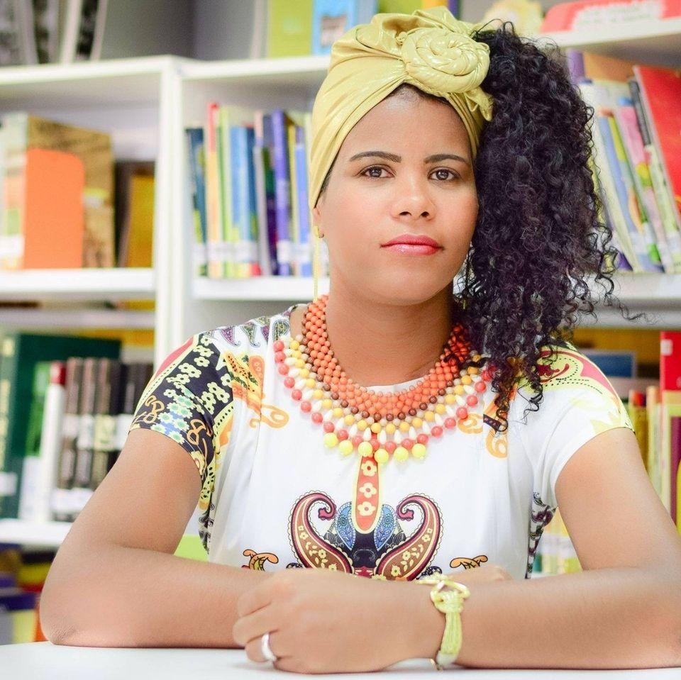 Mulher negra de vestido branco, colar afro e turbante de cor amarela. Estante de livros ao fundo.