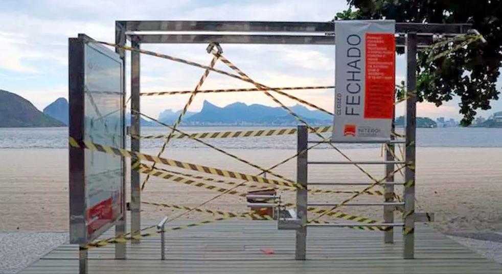 "Equipamento para exercícios físicos na praia de Icaraí interditado com um banner da prefeitura escrito ""fechado""."