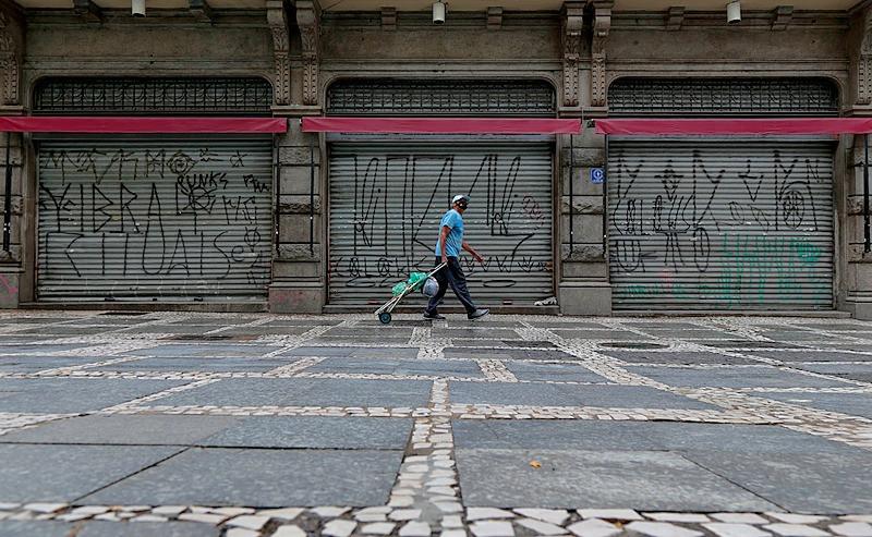 Homem no centro da imagem, sozinho, com um carrinho de compras, no meio de uma cidade fechada pelo lockdown