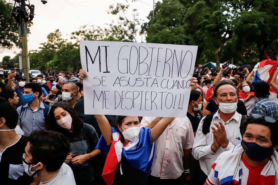 """Mulher paraguaia de máscara segura cartaz: """"Mi gobierno se asusta cuando me despierto"""""""