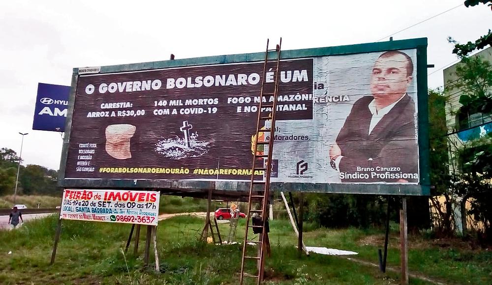 Outdoor entre rodovia e CIEP com escada escorada e imagem de uma nova mensagem aplicada pela metade. Imagem de fundo preto responsabilizando Bolsonaro pelo o aumento do preço do arroz, pelas mortes por covid e as queimadas na Amazônia e Pantanal.