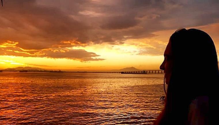 Pôr do sol com tons fortes da cor amarela e laranja em uma orla. Ao fundo a ponte Rio-Niterói e algumas embarcações. Eu estou do lado direito da imagem como uma sombra assistindo o pôr do sol.