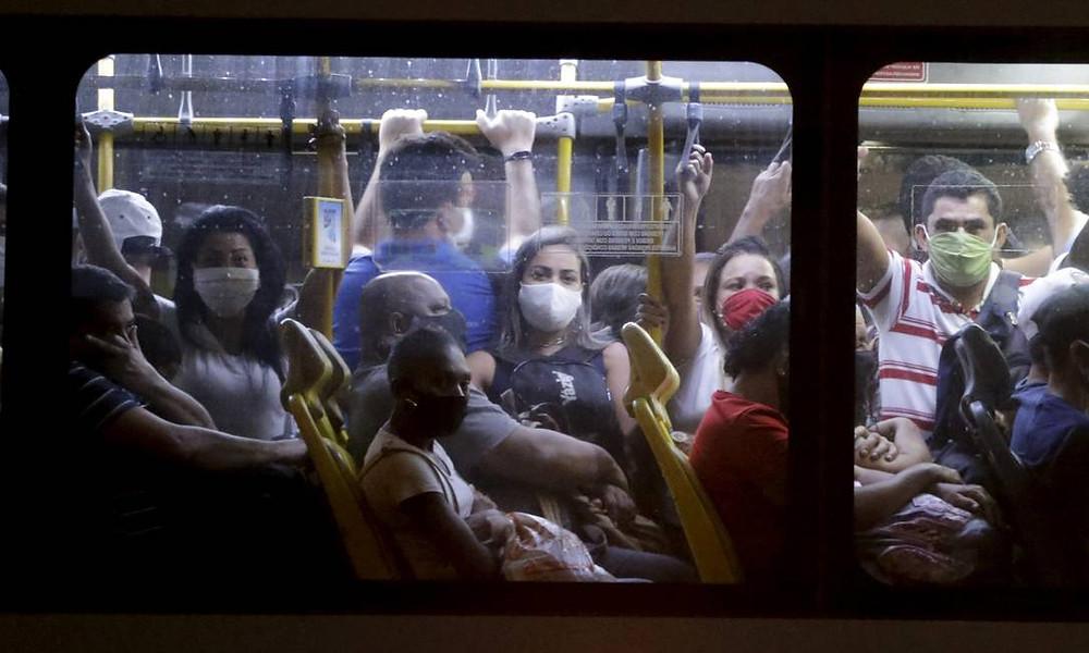 Ônibus lotado com janelas fechadas e pessoas de máscara.