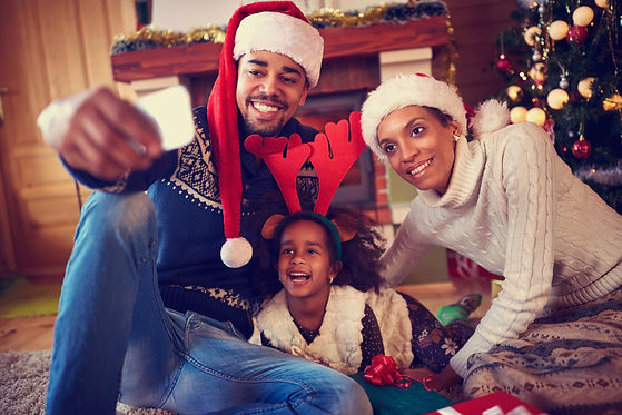 Smiling young family in Christmas atmosphere making photo with smartphone.jpg