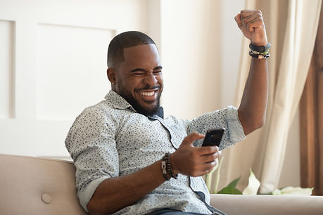 Excited overjoyed black man winner holding smartphone feeling euphoric with mobile online