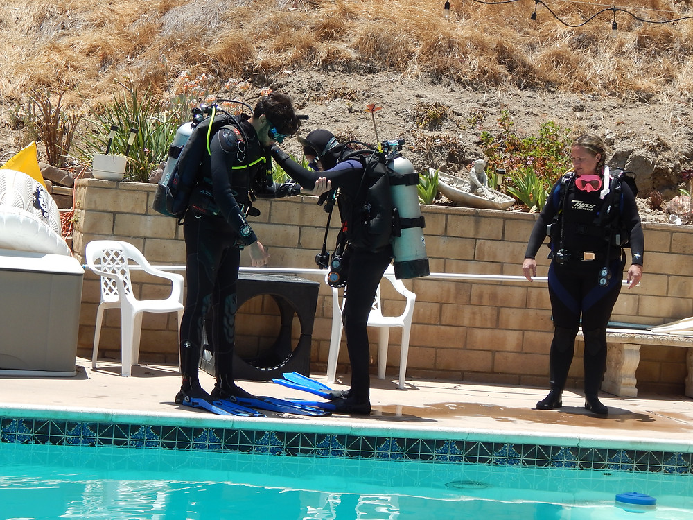Students conduct a pre-dive safety check prior to entering the water with a giant stride, an entry technique used by boat divers.