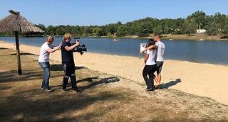 Making-of-Foto aus einer Filmproduktion der Bielefelder tri-ergon film-& werbeagentur für Leading Campings. Zwei Kameramänner filmen ein Pärchen am Sandstrand eines Badesees.