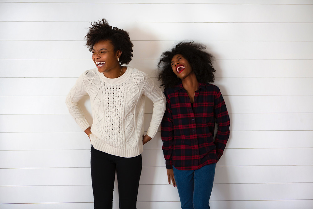 Two girls stand side by side and laugh with closed eyes