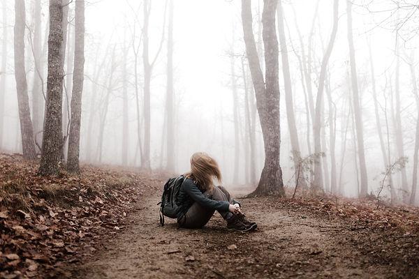 girl hiker sat down on woodland path.jpg