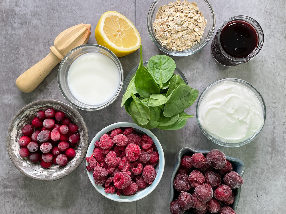 small bowls with smoothie ingredients including berries, yogurt, milk, spinach and oats