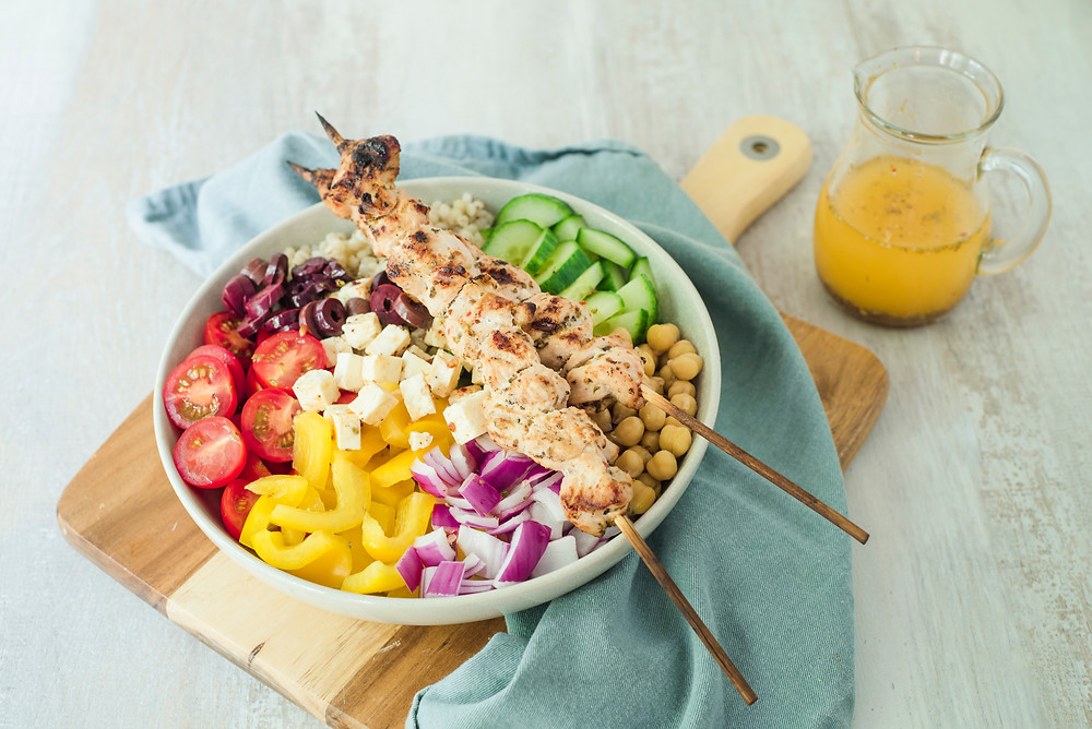 Mediterranean Nourish Bowl with cherry tomatoes, peppers, red onion, chickpeas, cucumber and olives topped with 2 grilled turkey skewers.