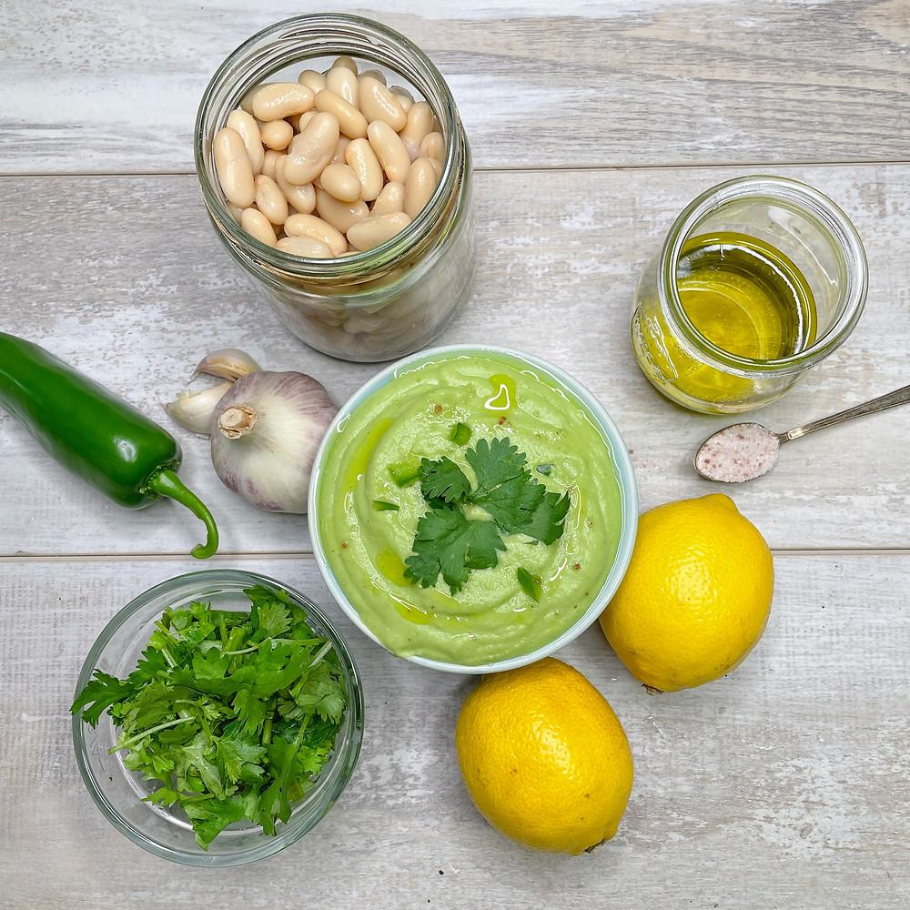 Dip ingredients including lemons, chopped cilantro, jalapeno, garlic, white beans, olive oil and salt