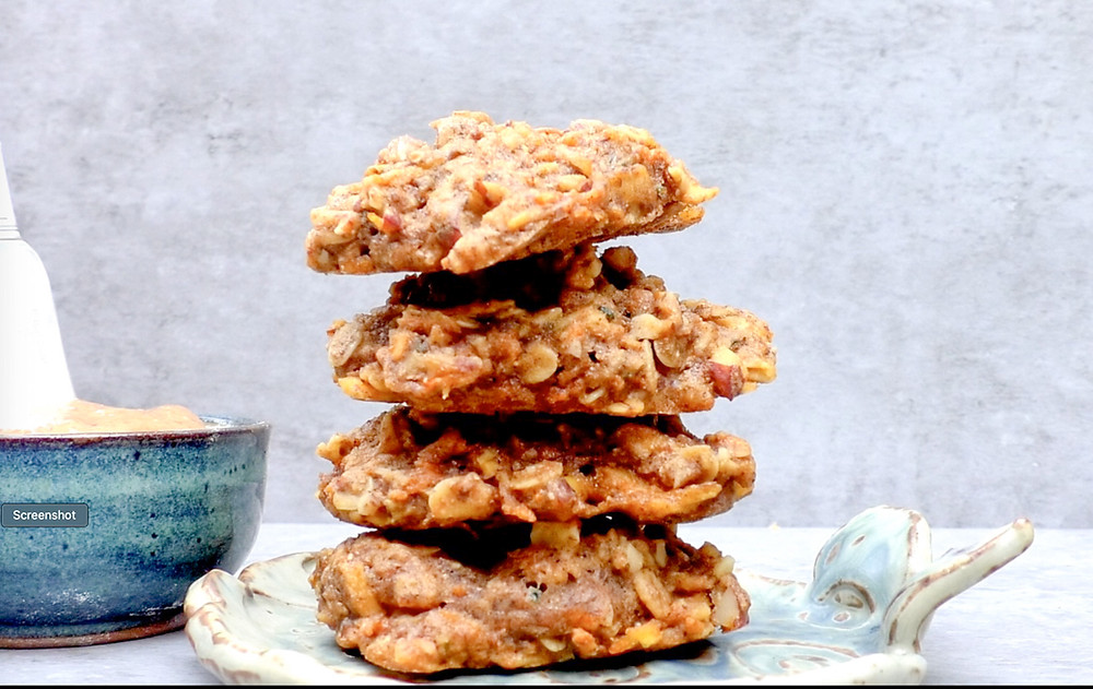 A stack of four apple pie muffin top cookies on a plate.