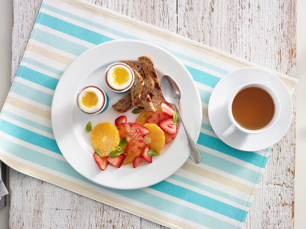 Soft boiled eggs with toast, fruit and tea