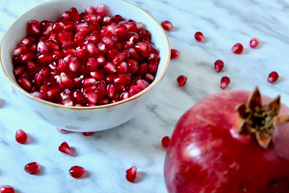 pomegranate with bowl of arils