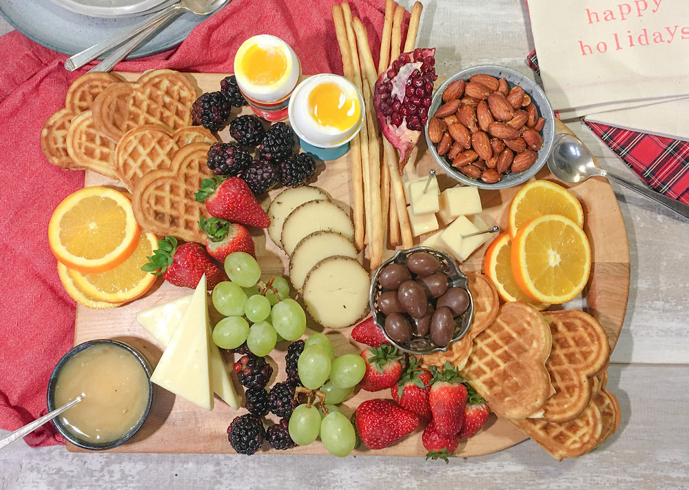 A board with waffles, fruit, cheese, 2 soft cooked eggs, almonds and a pot of honey.