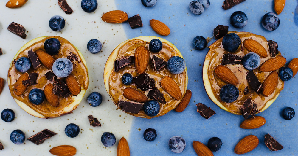 apple slices with almond butter, almonds, dark chocolate and blueberries