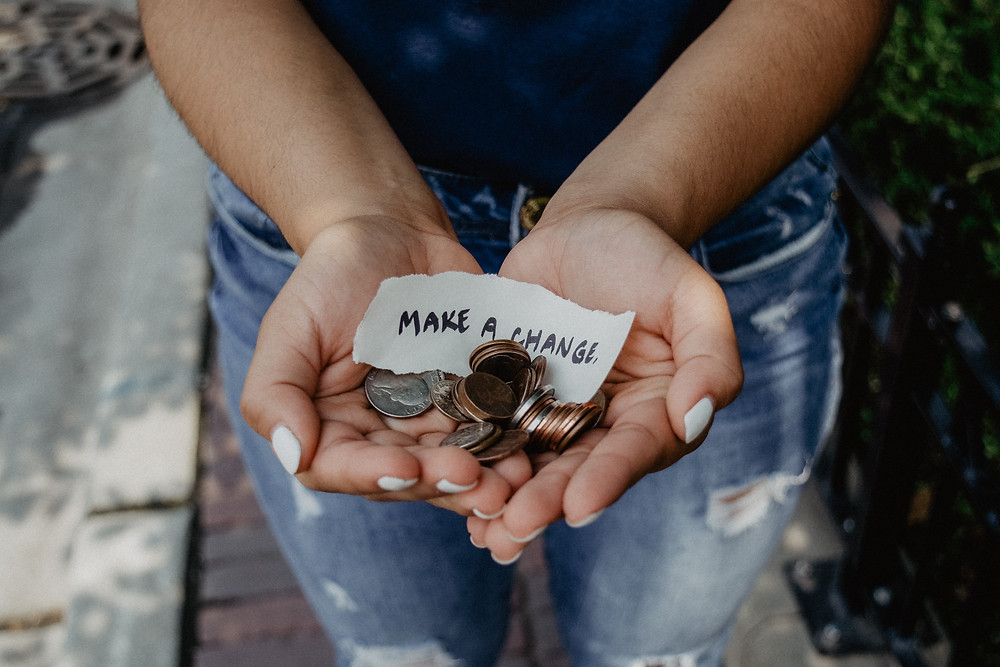 """Image, hands holding a pile of coins and a slip of paper that says """"make a change"""""""