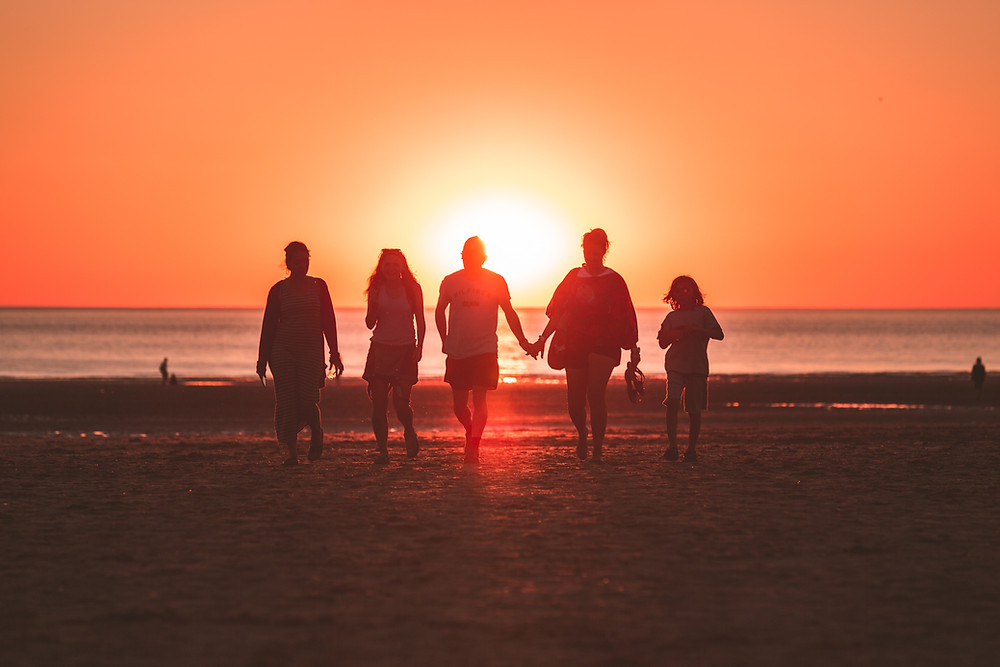 Image, people walking into a sunset on a beach
