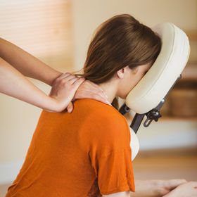 Young woman getting massage in chair in