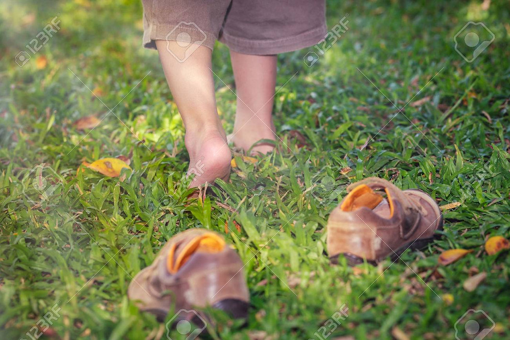 small barefoot child in field with pair of  brown shoes behind them