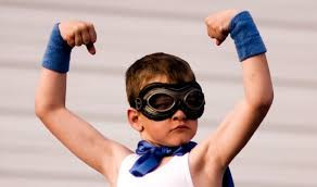 child wearing superhero costume, flexing arm muscles