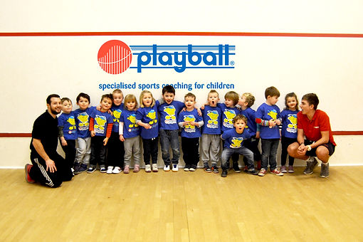 Children aged two to six years old on squash court with two adults